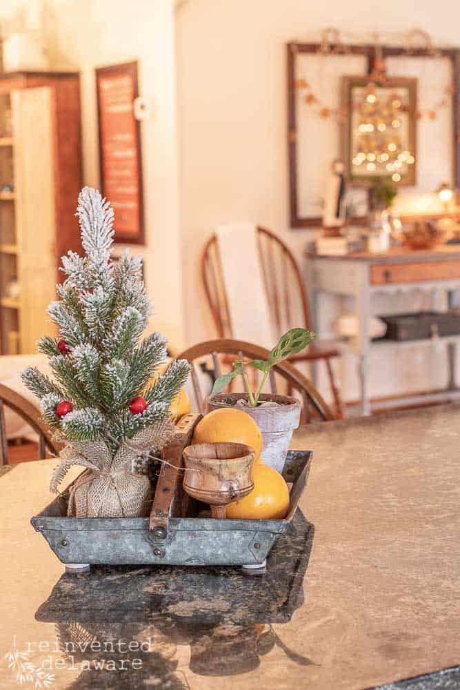 kitchen island showing vintage tool caddy filled with oranges, candle, small Christmas tree
