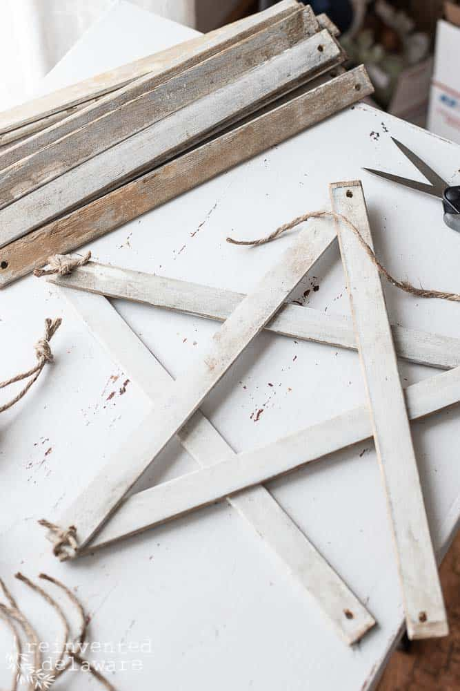 demonstration of tying jute on handmade farmhouse style stars to hold them together in the star shape