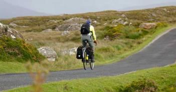Ein Mann auf einem Fahrrad, der auf einer Straße durch grüne Hügellandschaft fährt.