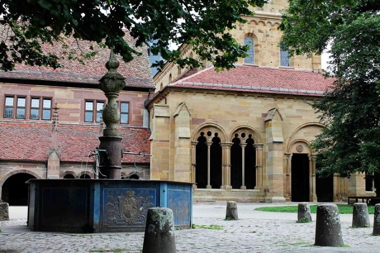 Direkt vor dem Eingang in die Klosterkirche. Wer genau hinschaut, kann sowohl Anteile aus der Romanik als auch Frühgotik in den Fenster- und Türbögen erkennen. Im Vordergrund der Klosterhofbrunnen.