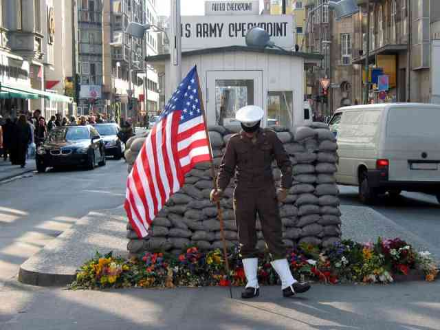 Soldat med amerikansk flag ved Checkpoint Charlie i Berlin