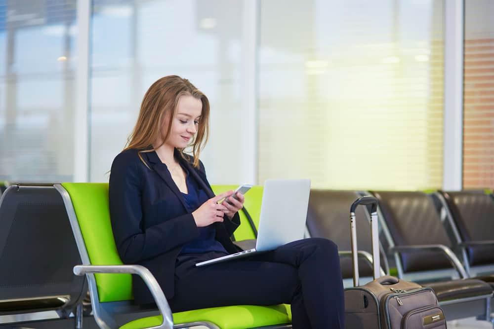 Ung kvinde som arbejder på computer og telefonen i lufthavnen.