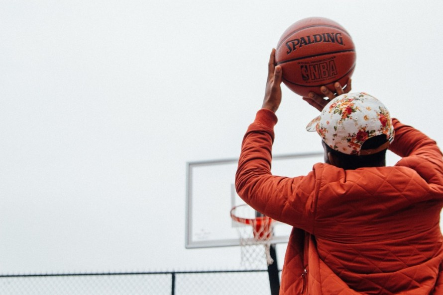 Dating Tips: Learn sports. Man wearing an orange jacket, shooting a basketball.