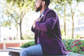 Black Men wearing purple blazer with jeans sitting down