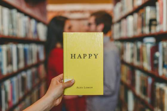 """Happiness image of a man and woman in a library aisle facing each other. Another person whose arm is visible, is holding a yellow book titled, """"happy,"""" by Alex Lemon."""
