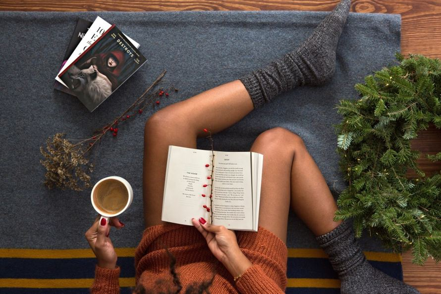 woman laying on the couch drinking coffee and reading a book