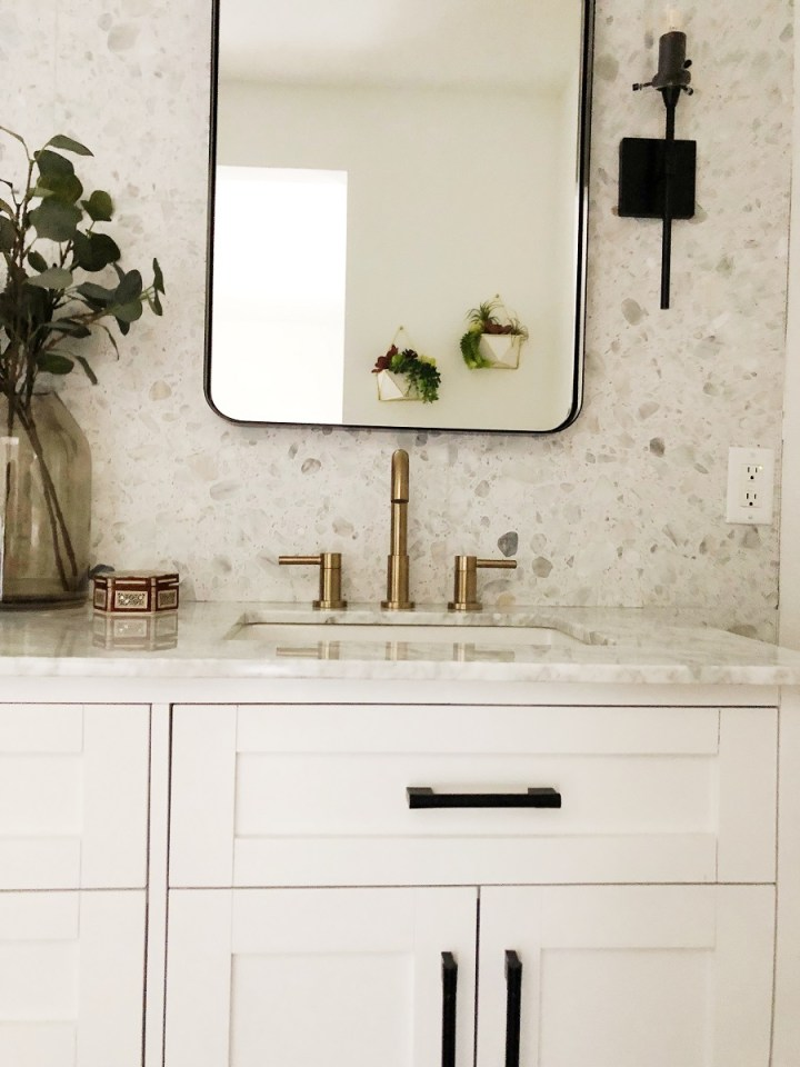 "White 72""bathroom vanity with black fixtures and brass sink hardware. Black vanity mirror. Ann Sacks Terrazzo tile."