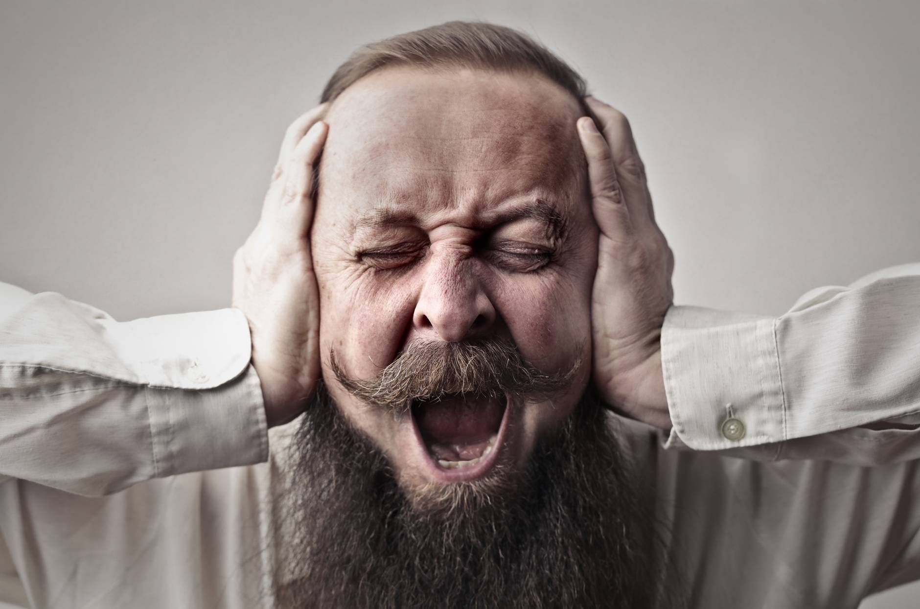 close up photo of screaming man with a full beard covering his ears and closing his eyes