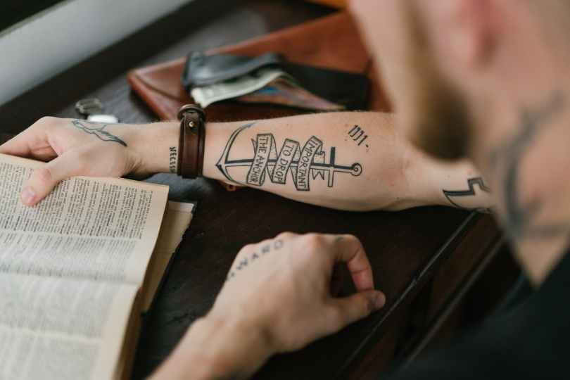 crop man with tattoo on arm reading old book