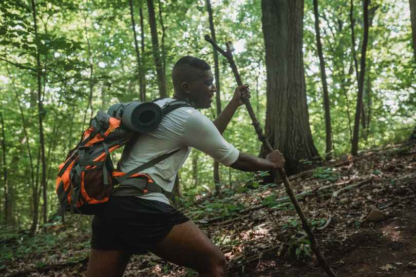 male backpacker trekking along forest slope with stick