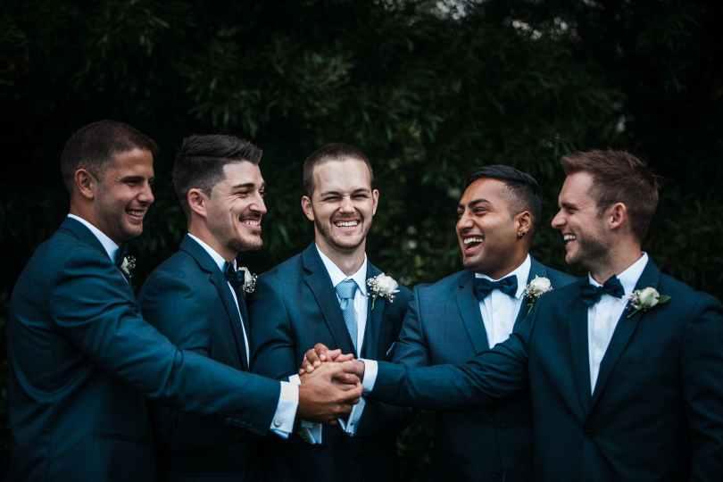 happy groom with groomsmen on street