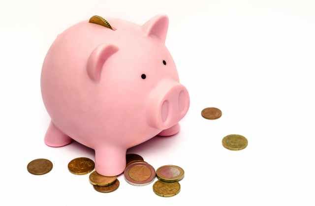 How to save for your childs future. Pink piggy bank surrounded by coins.