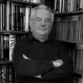 Ramsey Campbell author photo - The author is pictured in a long sleeved black top with his hands crossed stood in front of bookshelves.