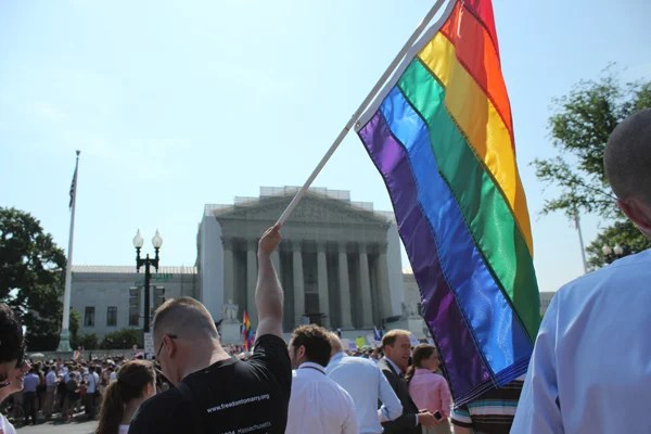 A man holds a gay pride flag in front of the Supreme Court on Wednesday (June 26, 2013) after the court decided to strike down the Defense of Marriage Act.  RNS photo by Adelle M. Banks