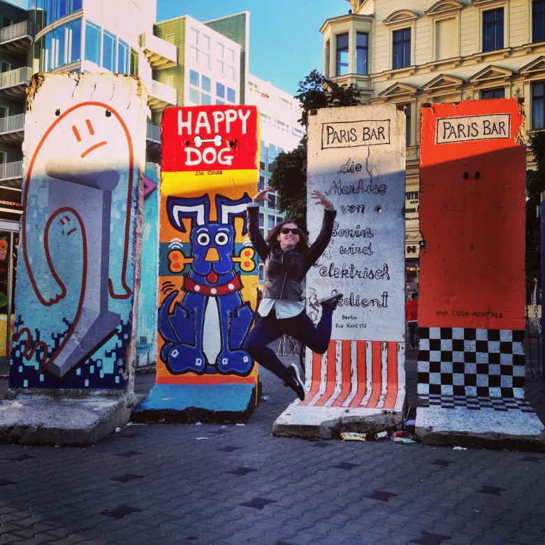 Jumping in front of painted pieces of the Berlin wall at Checkpoint Charlie.