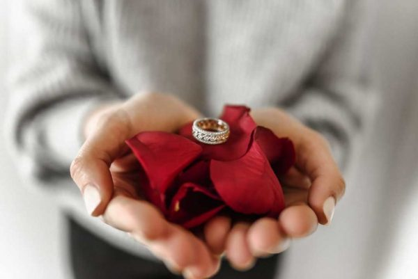 Man Holding an Engagement Ring in Red Petals - A Guide To A Successful Destination Marriage Proposal