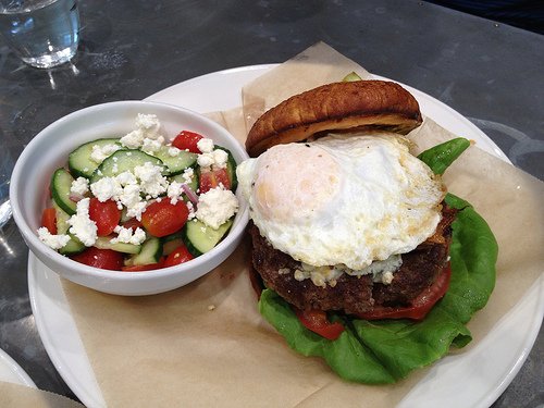 OE Restaurant pork belly burger, with egg on top, pretzel bun, and veggie salad