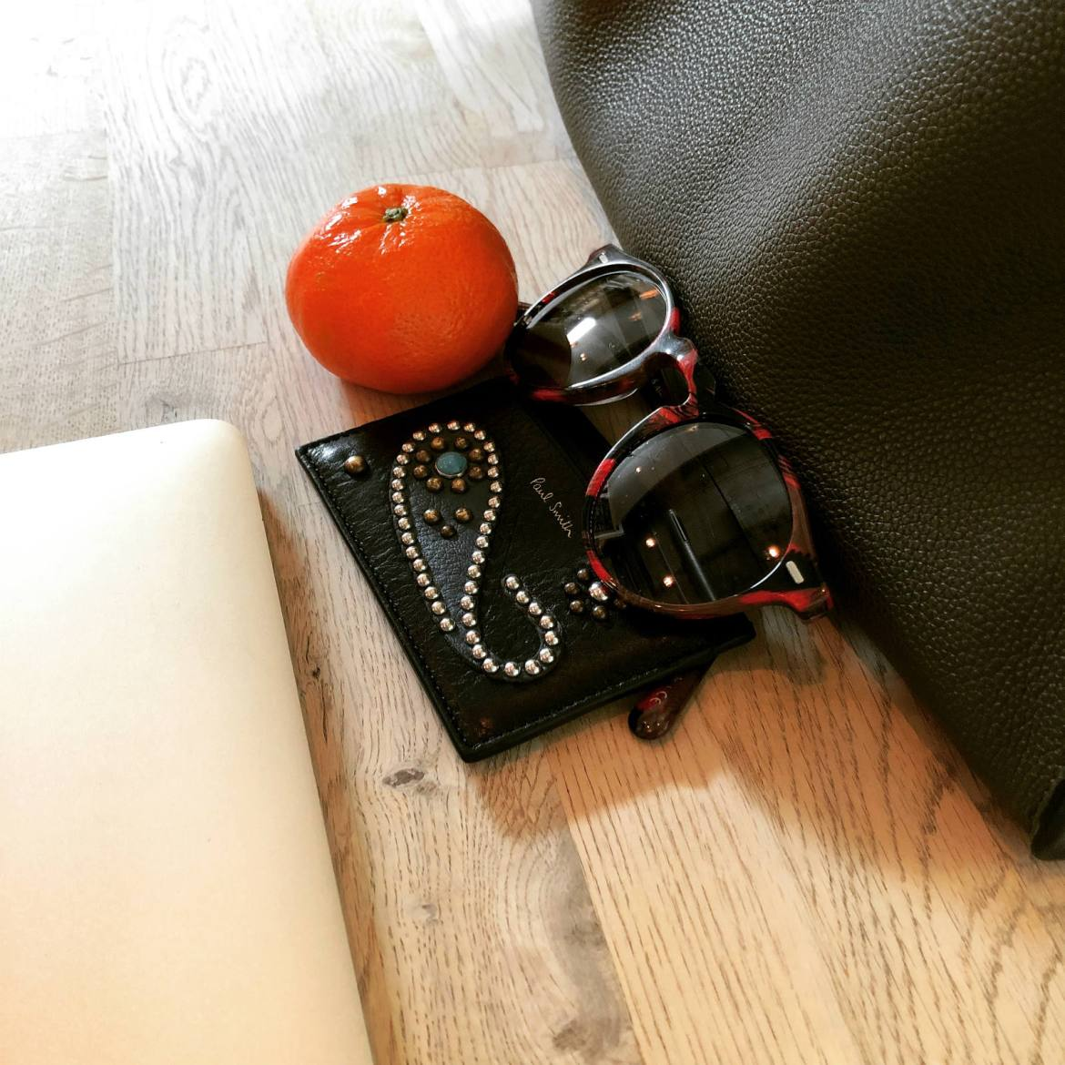 Friday afternoon still life: gold MacBook, Paul Smith studded paisley card holder, a wintertime clementine, vintage glass red and gray Oliver Peoples x Alain Mikli sunglasses, and olive pebbled leather Prada tote. At Victory Coffee in Tampa's Channel District.