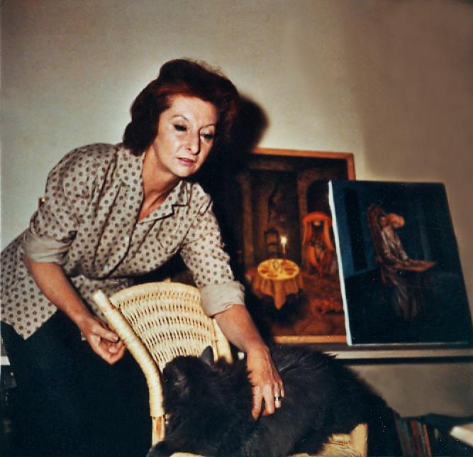 (Foto:Remedios Varo en su estudio con su gato Zorrillo. Al fondo sus cuadros Presencia Inquietante y Visita Inesperada - foto de Kati Horna 1959)