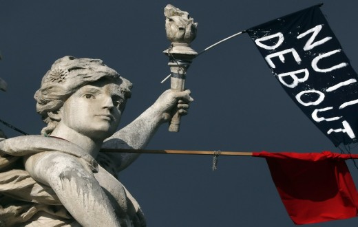 """A red flag and a black one reading """"Nuit Debout"""" (Rise up at Night) are seen on a statue place de la Republique in Paris"""