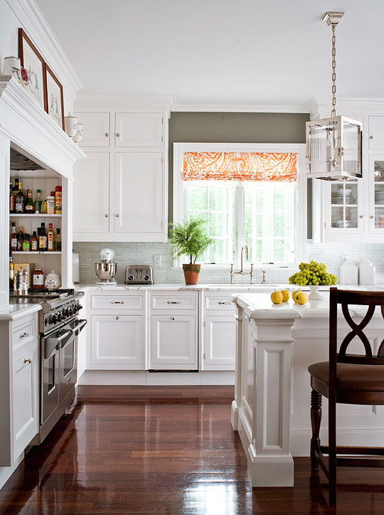 gray and white kitchen with orange curtains