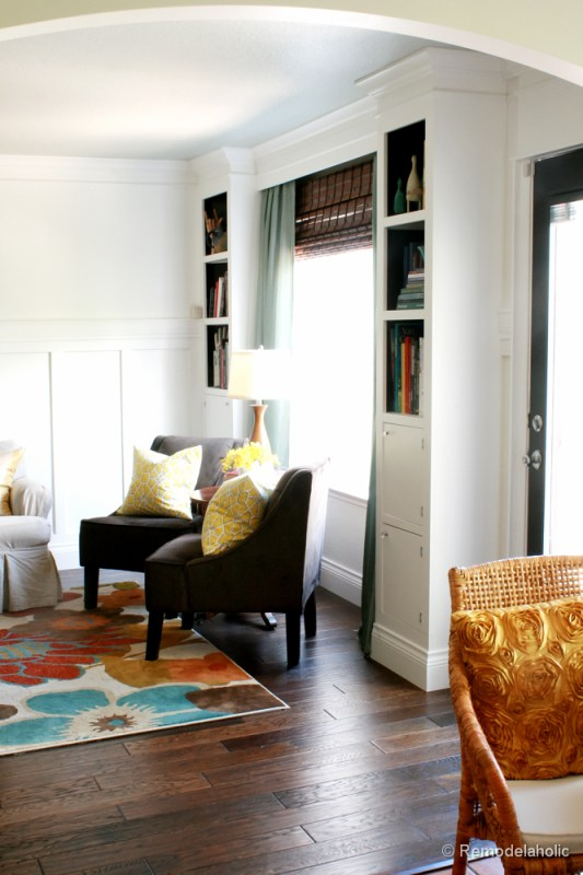 Living Room Remodel with yellow accents wood floors and built-in bookcases and columns with arches-13