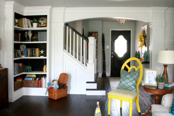 Living Room Remodel with yellow accents wood floors and built-in bookcases and columns with arches-24