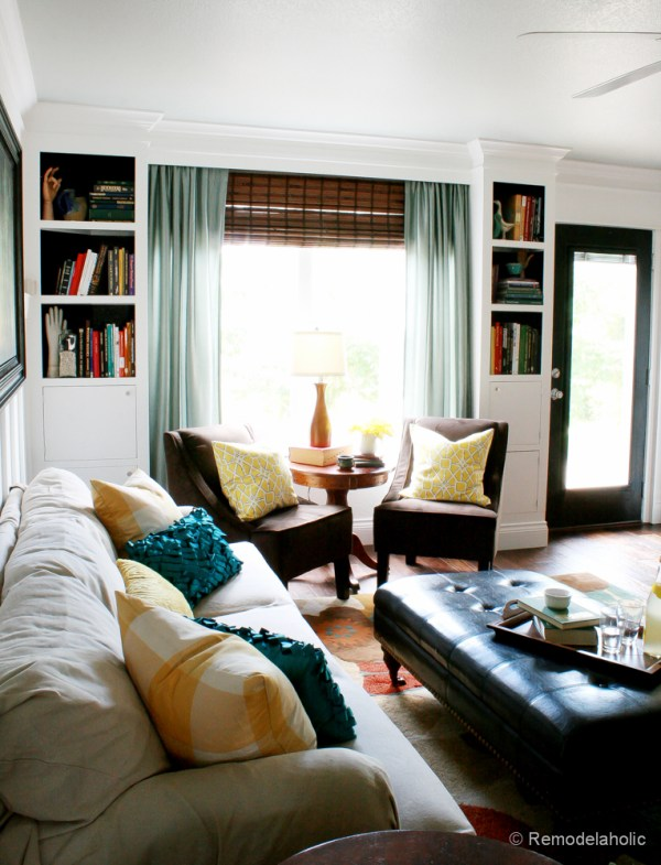 Living Room Remodel with yellow accents wood floors and built-in bookcases and columns with arches-36
