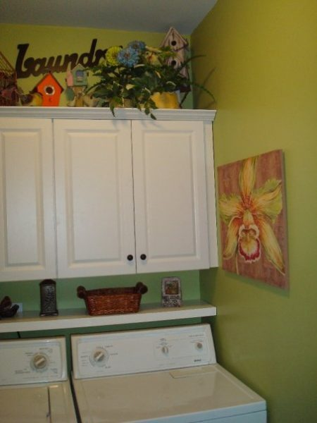 small green laundry room with floating shelf and cabinets, Southern Hospitality
