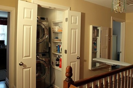 tiny hallway laundry closet with stacked washer and dryer and wall cubbies, The Yummy Life