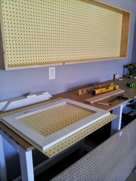 building sliding doors for the pegboard tool cabinet, featured on Remodelaholic.com