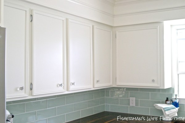 glass knobs and molding on white kitchen cabinets with glass subway tile backsplash, Fisherman's Wife Furniture featured on Remodelaholic.com
