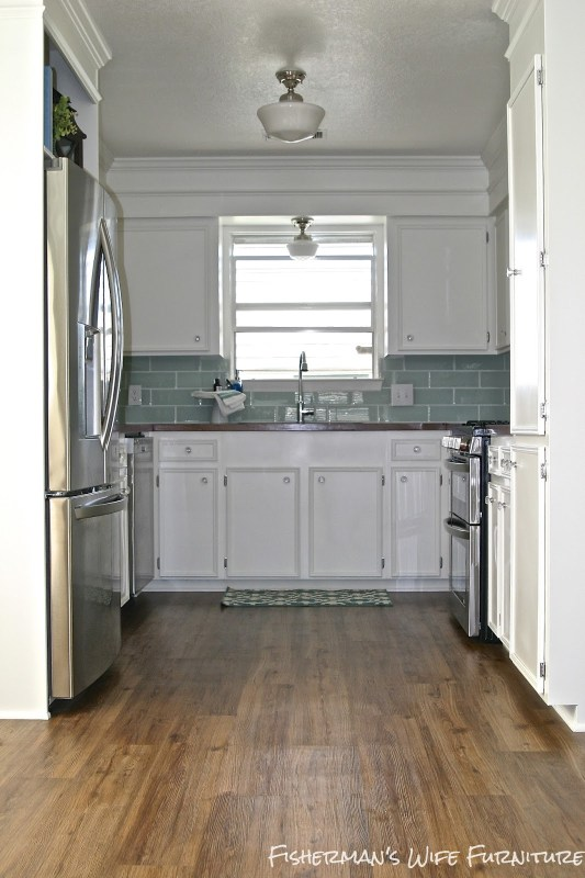 Small White Kitchen Makeover with Built-In Fridge Enclosure, Fisherman's Wife Furniture featured on Remodelaholic.com #kitchen #built-in #butcherblock #subwaytile #vinylflooring