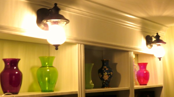 colorful glass and lighted sconces on built-in bookcase, Home Is Where My Heart Is featured on Remodelaholic