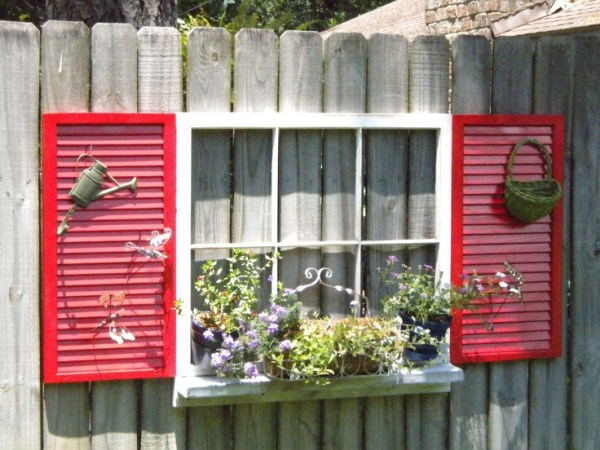 source unknown - old window with sill and shutters on fence - via Remodelaholic