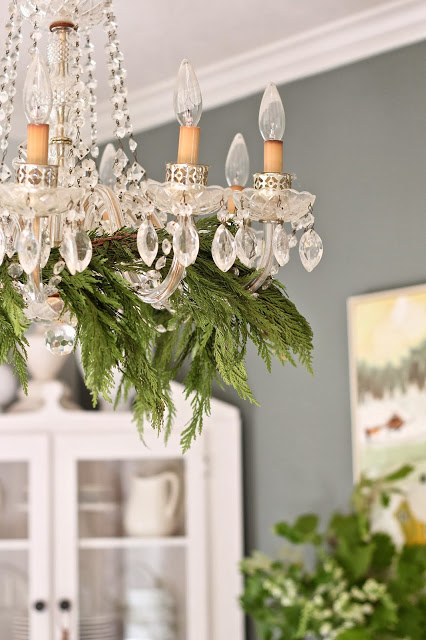 add fresh evergreen boughs to the chandelier - Curious Details via @Remodelaholic