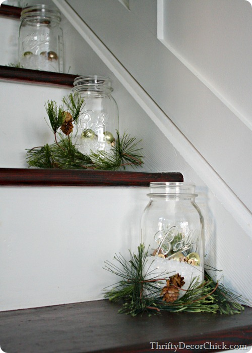 use evergreen springs and mason jars to decorate the stairs for Christmas - Thrifty Decor Chick via @Remodelaholic