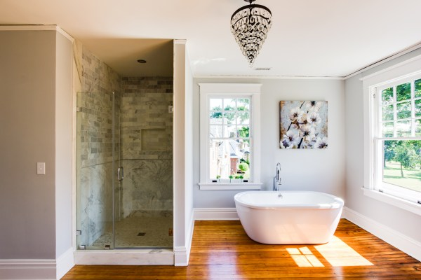 (Hawthorne) spacious open bathroom with wood floor, walk in marble shower, and white basin tub @Remodelaholic
