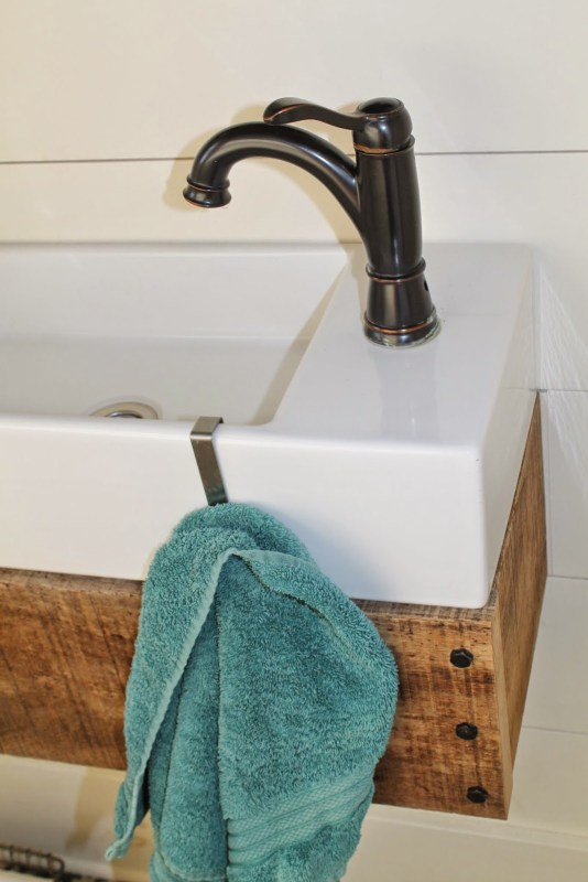 towel holder on IKEA sink with diy floating vanity - Girl Meets Carpenter featured on @Remodelaholic