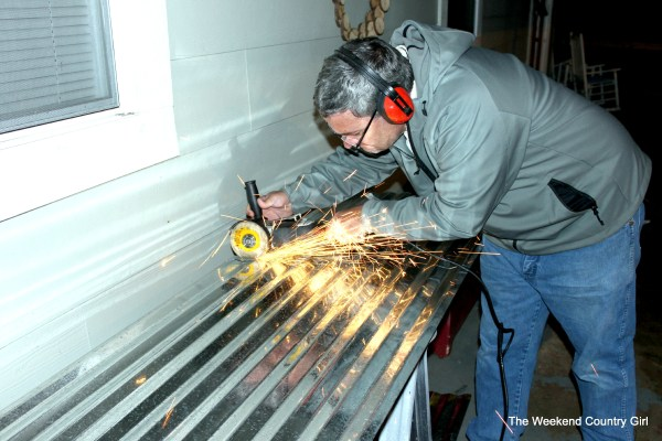 cutting corrugated tin for a wall treatment - The Weekend Country Girl featured on @Remodelaholic