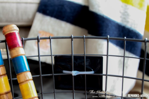 use a rolling wire basket to organize sports gear and toys - The Heathered Nest on @Remodelaholic