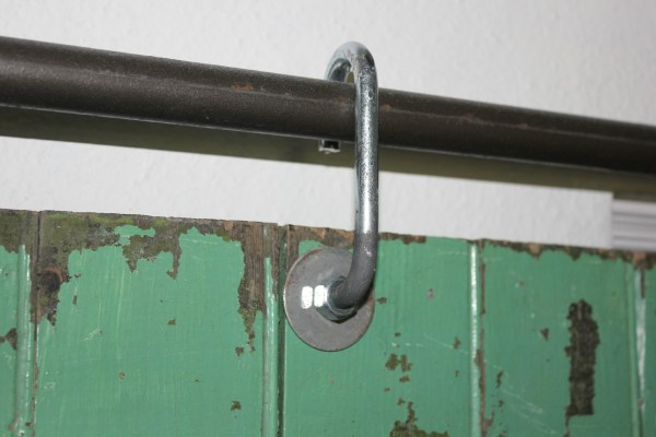 salvaged door hung on a sliding barn hardware made from black pipe and J hooks - Cottage 4C