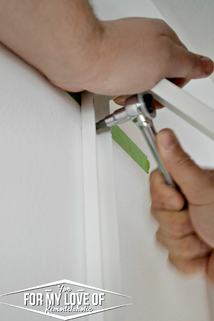 use a socket wrench and phillips head bit to tighten the screws into place through the bracket