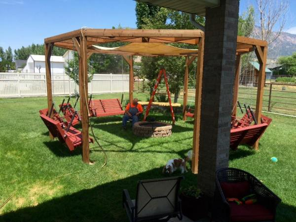 DIY round pergola with swings, firepit and shade screen featured on  @Remodelaholic - Remodelaholic Tutorial: Build An Amazing DIY Pergola And Firepit