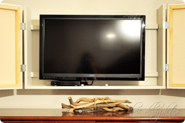 build a frame and box to hide the television behind hinged art canvas doors (dixiedelights)