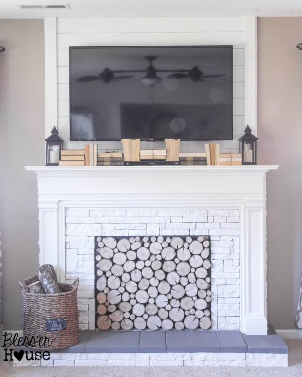faux fireplace with storage inside and books to hide cords (Blesser House on Remodelaholic)