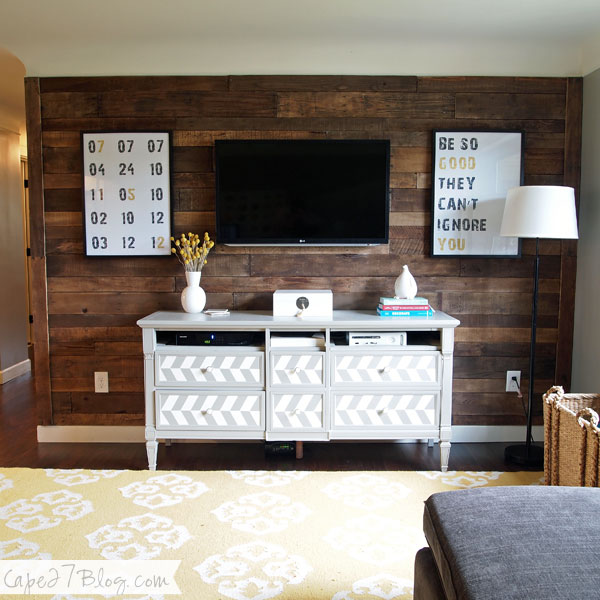 symmetrical canvases around the television, on a stained wood plank wall (Cape 27 Blog)