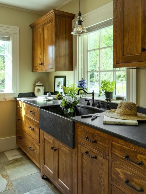 beautiful kitchenw ith wood cabinets and black countertops and apron sink (via HGTV)