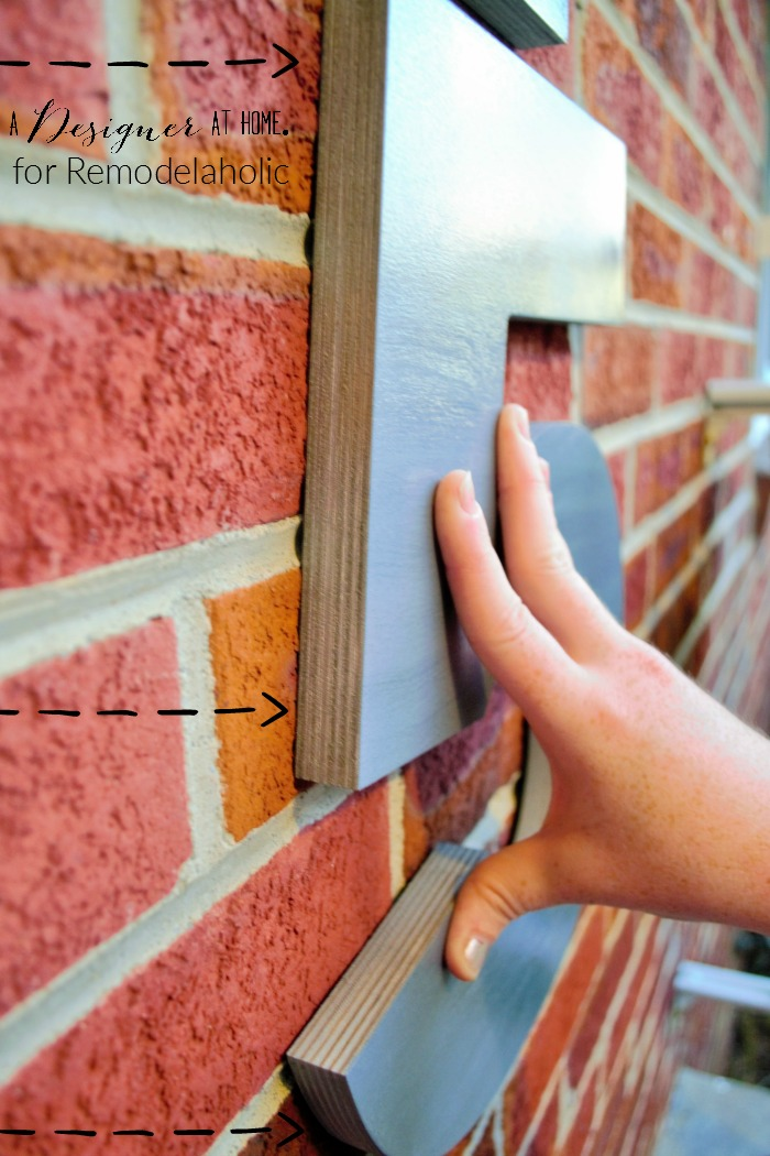 hanging large house numbers on brick