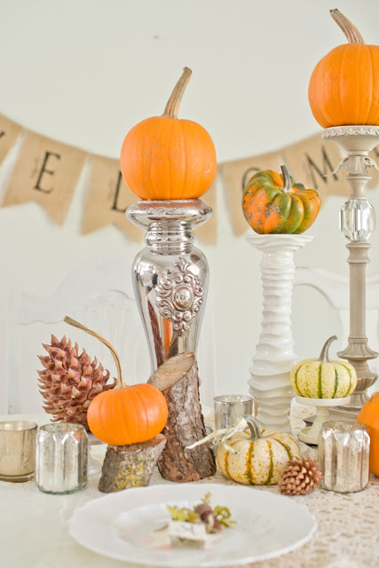 pumpkin centerpiece using tall candlesticks and cut logs and mercury glass Domestic Fashionista